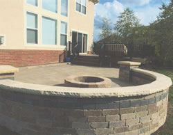 Curved seating wall enclosing the deck and firepit.