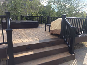 Wooden deck with spa leading down to path.