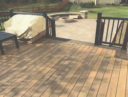 Wooden deck with stairs leading to pave patio with fire pit.